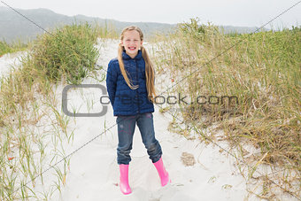 Full length portrait of a smiling girl at beach
