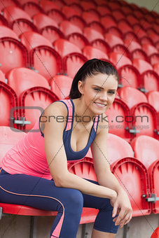 Smiling toned woman sitting on chair in the stadium