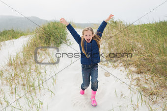 Full length of a cheerful girl running at beach