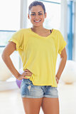 Portrait of a smiling fit young woman in yellow top