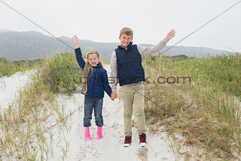 Happy siblings standing hand in hand at beach