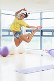 Young woman jumping in fitness studio