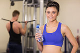 Woman with water bottle while man using lat machine in gym