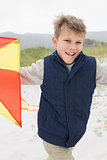 Portrait of cheerful boy with kite at beach