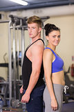 Sporty woman and man standing back to back in gym