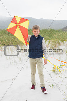 Portrait of a happy boy with kite at beach