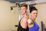 Sporty couple gesturing thumbs up in the gym