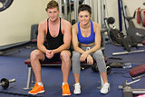 Sporty young man and woman sitting in the gym