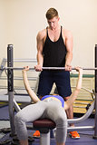 Trainer helping woman to lift the barbell bench press in gym