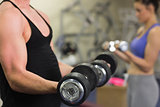 Man and woman using dumbbells in the gym