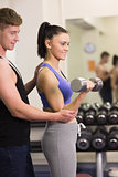 Male trainer helping young woman with the dumbbells in gym