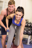 Male trainer helping woman with dumbbell in the gym