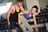 Trainer helping young woman with dumbbells in the gym