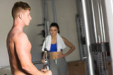 Woman looking at determined man use the lat machine in gym
