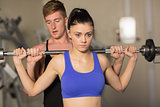 Trainer helping fit woman to lift the barbell in gym