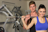 Male trainer helping fit woman to lift the barbell in gym