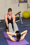 Trainer helping woman do abdominal crunches  at a gym
