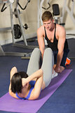 Trainer helping woman do abdominal crunches  at gym