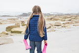 Girl holding her wellington boots at beach