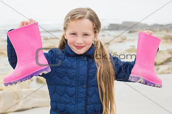 Cute smiling girl holding her wellington boots at beach