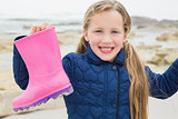 Cute girl holding her wellington boot at beach