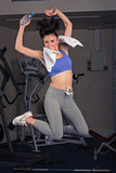 Full length portrait of fit woman jumping in gym