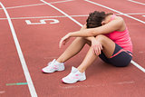 Tensed sporty woman sitting on the running track