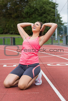 Toned woman doing stretching exercise on the running track