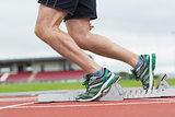 Low section of a man ready to race on running track
