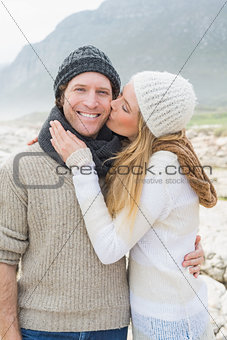 Woman kissing a man on rocky landscape