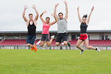 Fit people jumping on ground against the stadium