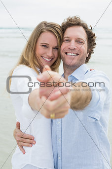 Happy young couple dancing at beach
