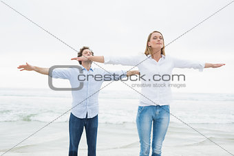 Casual couple with eyes closed at beach