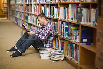 Focused young student sitting on library floor using tablet
