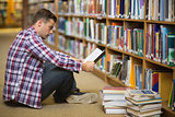 Handsome young student sitting on library floor reading book