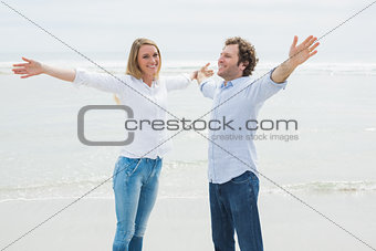 Happy couple stretching hands out at beach
