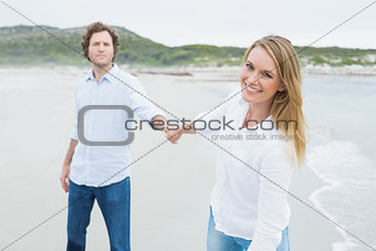 Smiling casual couple holding hands at beach