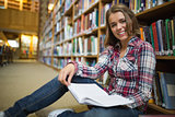 Smiling pretty student sitting on library floor reading book