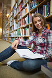 Smiling pretty student sitting on library floor holding book