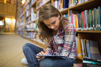 Pretty student sitting on library floor using tablet