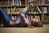 Pretty student lying on library floor reading book