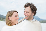 Smiling couple wrapped in blanket at beach