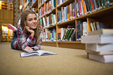 Pretty cheerful student lying on library floor reading book