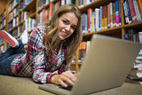 Young smiling student lying on library floor using laptop