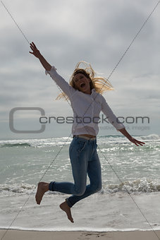Casual young woman jumping at beach