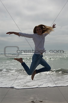 Full length of casual woman jumping at beach
