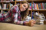 Smiling student lying on library floor using tablet pc