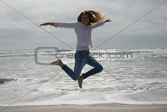 Full length of a casual woman jumping at beach