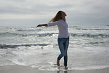 Woman with eyes closed and arms outstretched at beach