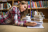 Smiling student lying on library floor reading